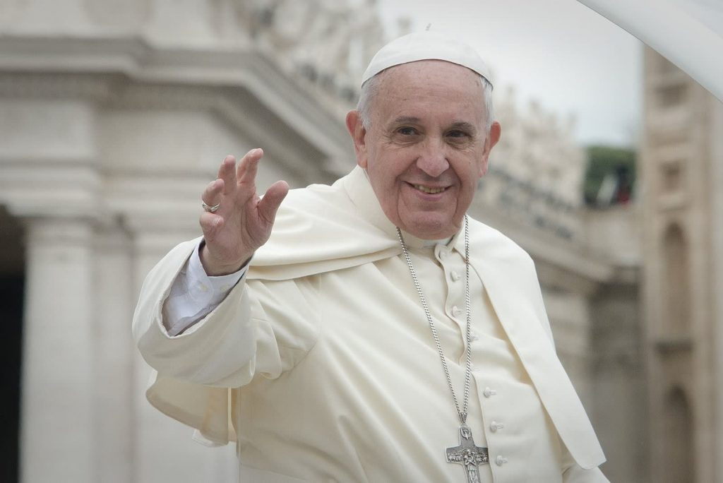 pope in white cloak and hat waving